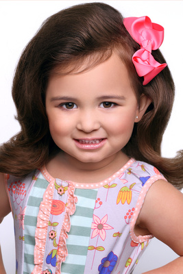 pageant headshot kid portrait girl curly brown hair smile pink bow